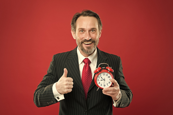 man in suit giving thumbs up and holding a clock