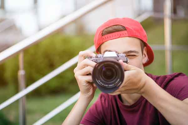 Young man taking pictures for school website