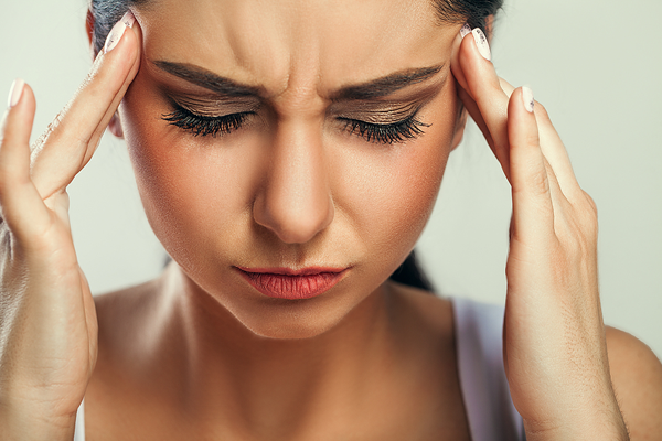 Woman holding head due to stress