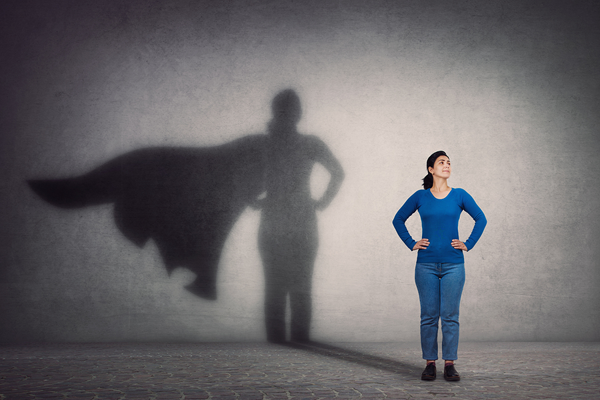 woman with hands on hips and shadow showing a heros cape