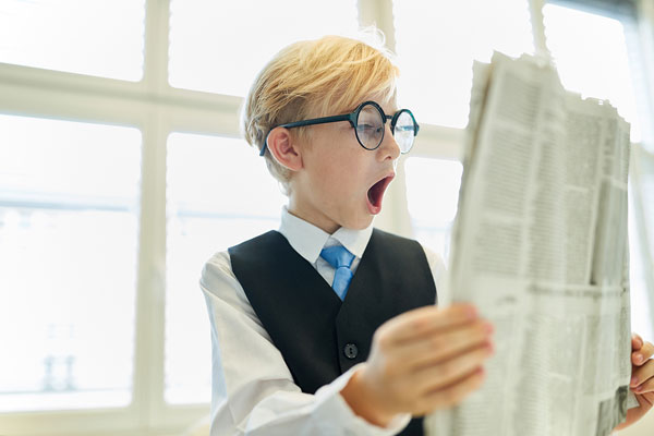 male student reading newspaper