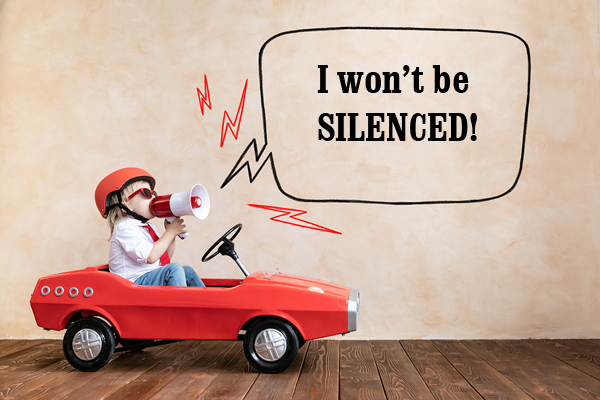 Little boy in toy car with megaphone saying I will not be silenced