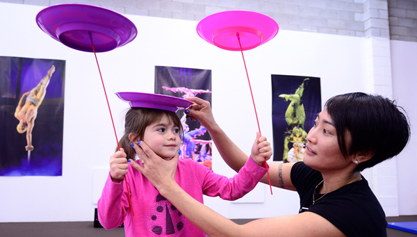 girl student learning to balance spinning plates