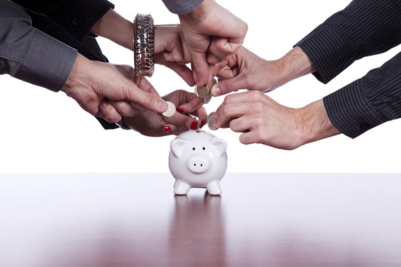 school administrators saving money in a piggy bank