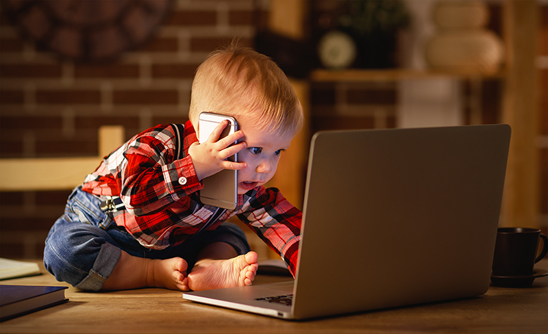 Photo of baby using laptop and cellphone