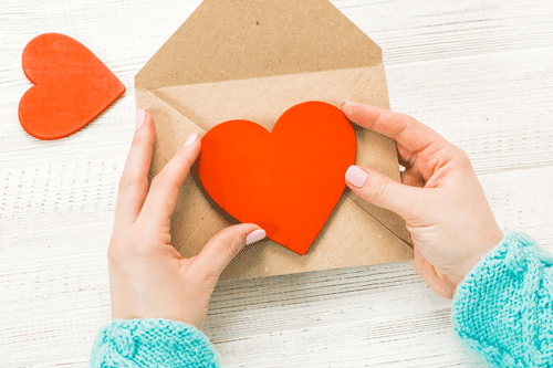 Image of student holding red paper heart
