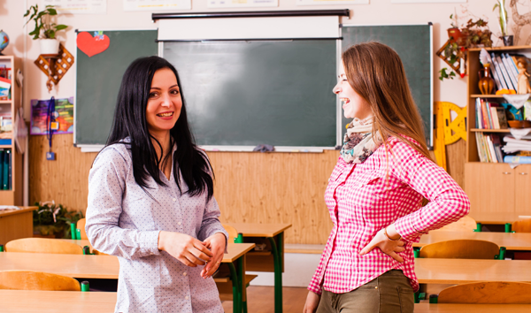 Parent and teacher smiling in a classroom