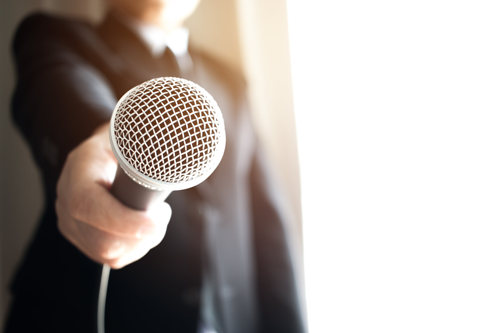 Microphone pointed at audience, asking for a testimonial