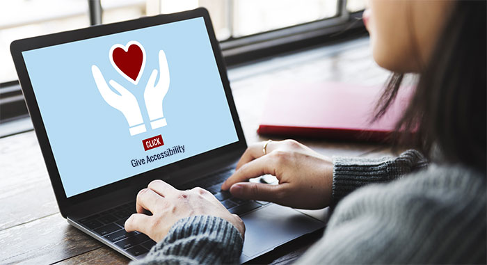 laptop screen showing two hands holding heart with text below that says Give Accessibility