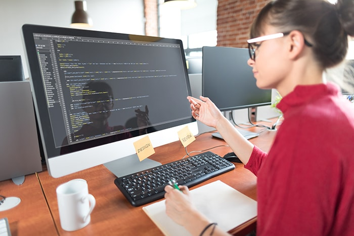 female working in code on desktop