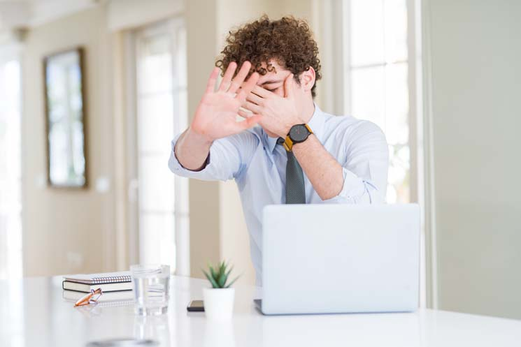 man at desk covering face and holding hand up to stop
