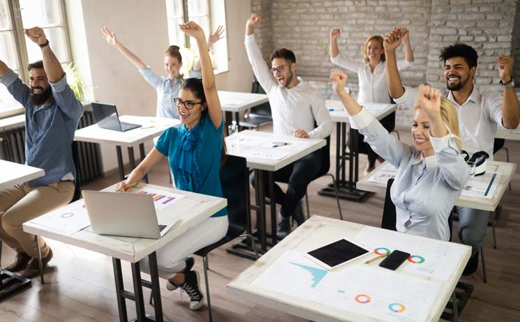 Classroom of adults sitting at desks with hands raised showing success