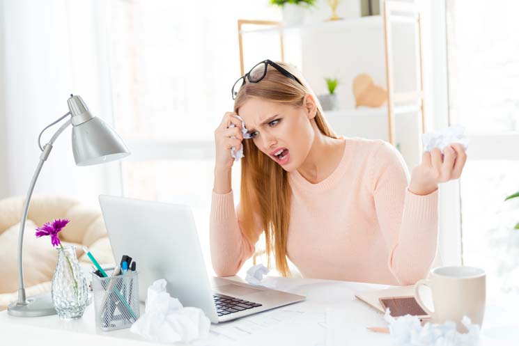 Lady in front of laptop with upset and confused expression