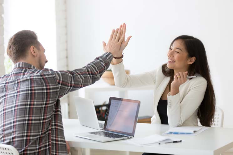 Male and female coworker giving a high five after collaborating accessibly