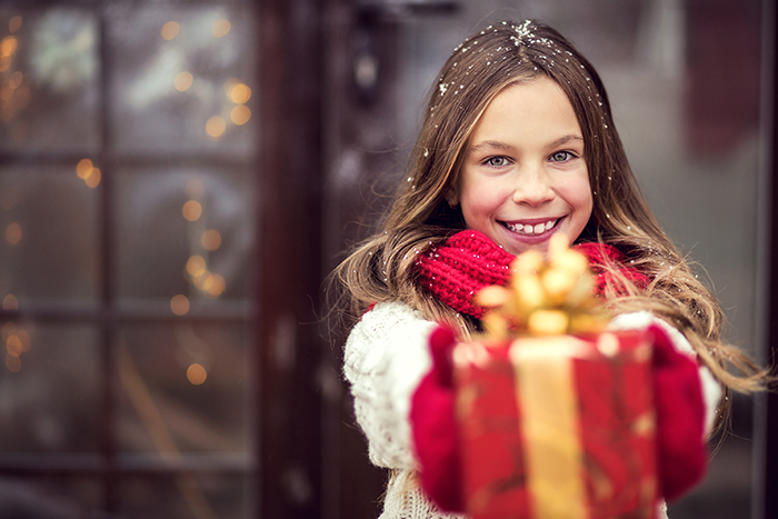girl giving a Christmas gift
