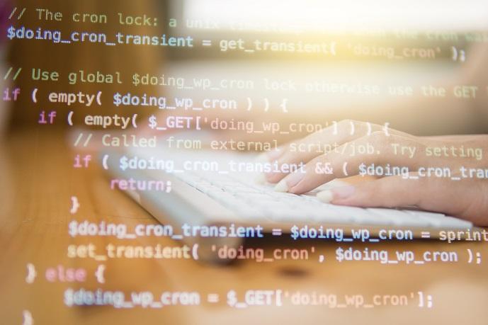 computer code on screen overlaying keyboard