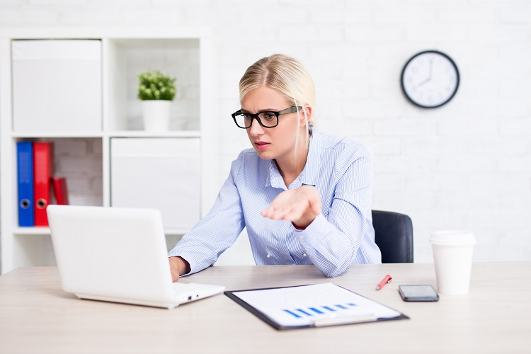 lady sitting at desk looking confused at laptop