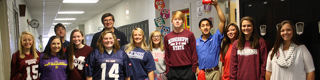 Students pose together wearing t-shirts from colleges
