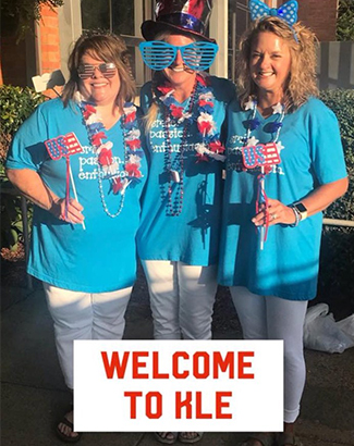 Teachers wear patriotic attire above the text Welcome to KLE