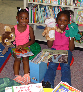 Two female students hold up their stuffed toys