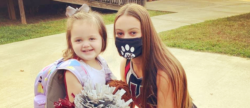 Cheerleader with face mask next to happy younger student