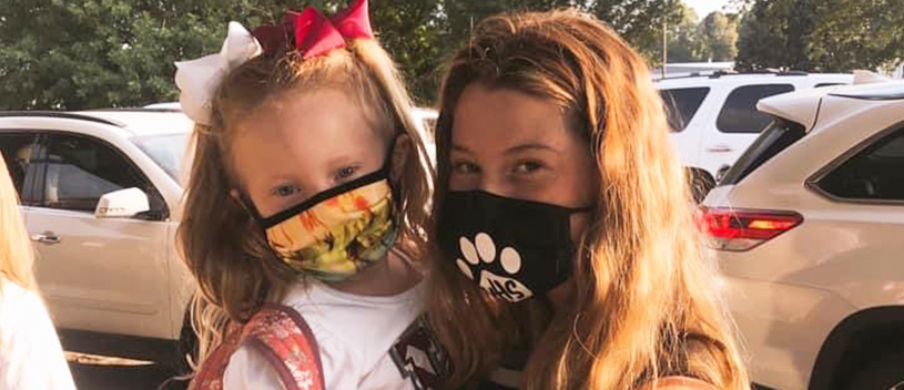 Spirited teen posing for a picture with an elementary student wearing face mask