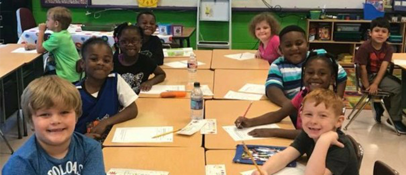 Kosciusko Lower Elementary School Students Smile as they Sit at their Classroom Table