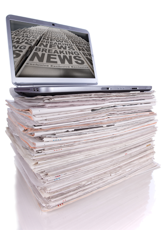 stack of newspapers with laptop on top