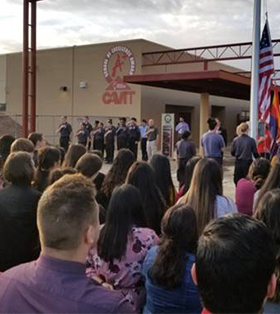Students and staff give the Pledge of Allegiance in front of CAVIT