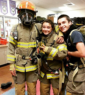 Students in firefighter outfits smile and pose together