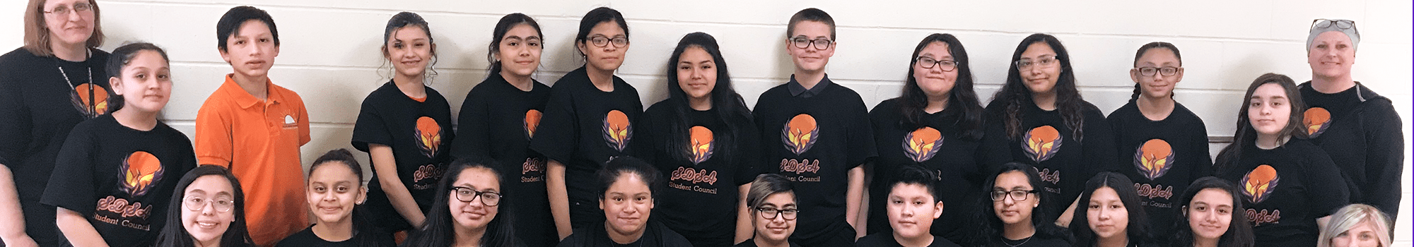 Happy Salida del Sol students posing for a picture with their teacher wearing black t-shirts