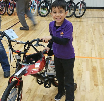 Happy Salida del Sol school boy with a new bike