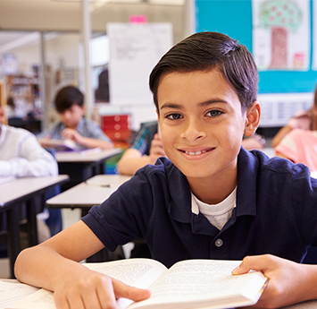 Proud school boy sitting at a desk