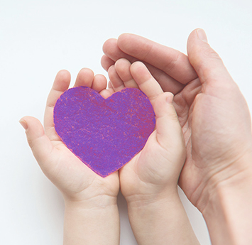 Adult hand supporting child's hands with a purple paper heart