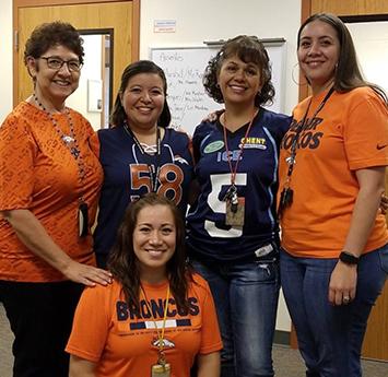Group of happy Salida del Sol staff members wearing orange and purple attire
