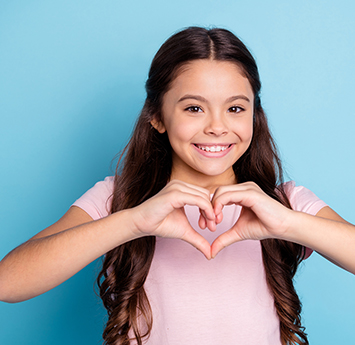 Happy school girl holding her hands in the shape of a heart