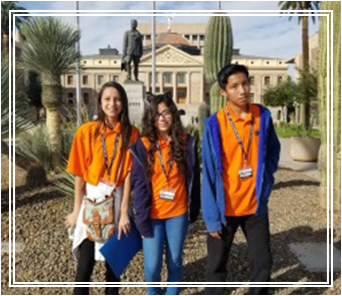 Three Aguila Middle school students wearing their orange t-shirts posing for a picture outside