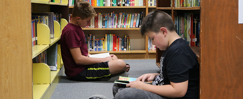 Two students sitting and reading in the library