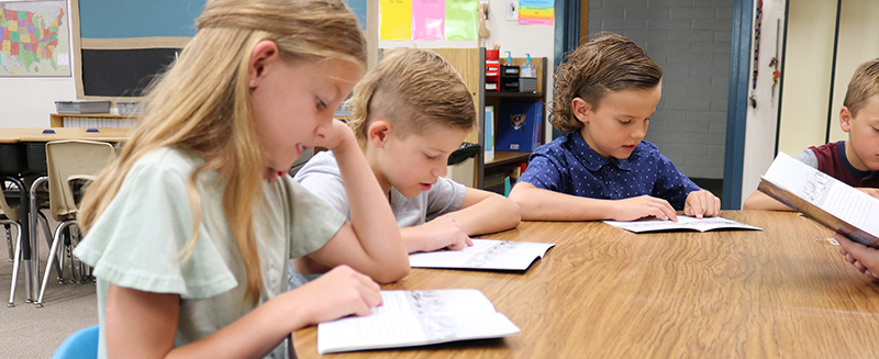 Students reading at a round table in classroom