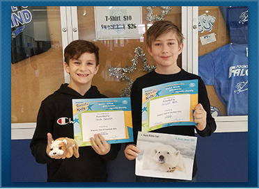 2 male students showing their awards