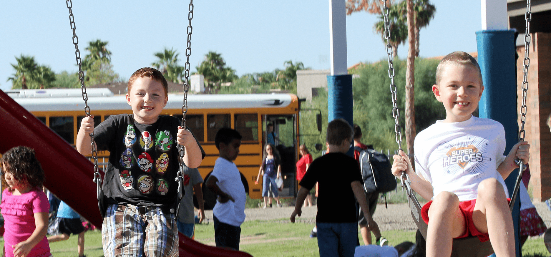 Two happy students swinging on the playground