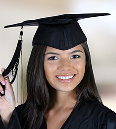 Student wearing a mortar board plays with her tassel
