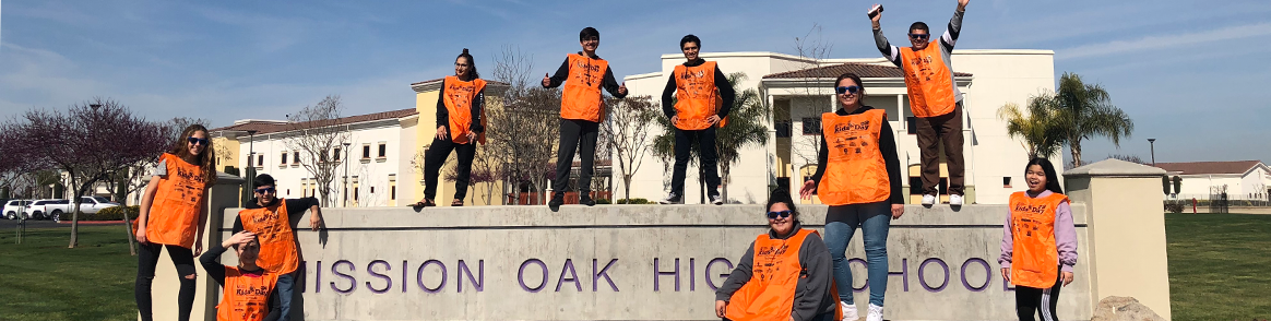 Group of students wearing Kids Day aprons and posing in front of the Mission Oak High School sign