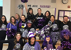 Group of staff members in school spirit attire posing together