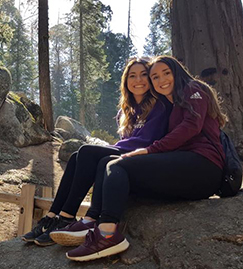 Two high school girls outside on a field trip in the woods
