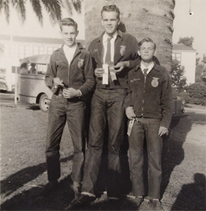 black and white photo of three FFA members holding ribbons
