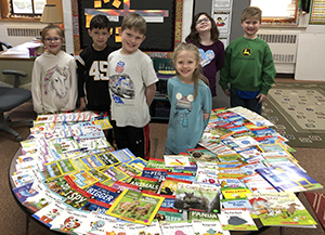 students with a table full of new books in the library