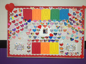 Bulletin board of thank you notes and hearts for Josh and John