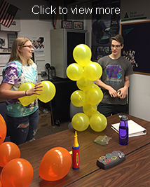 Female and male student stand near a balloon tower