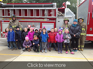 Students and teachers pose with firefighters in front of their truck
